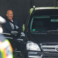 US actor Bruce Willis (C) is seen among members of the cast as he leaves the scene with a car after a shooting day of the fifth piece in the Die Hard series titled Good Day to Die Hard during a shooting day in Budapest, Hungary on May 19, 2012. ATTILA VOLGYI