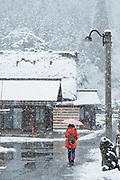 Woman walking with umbrella on snowy street,