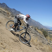 Jonas Meier from Christchurch in action during the New Zealand South Island Downhill Cup Mountain Bike series held on The Remarkables face with a stunning backdrop of the Wakatipu Basin. 150 riders took part in the two day event. Queenstown, Otago, New Zealand. 9th January 2012. Photo Tim Clayton