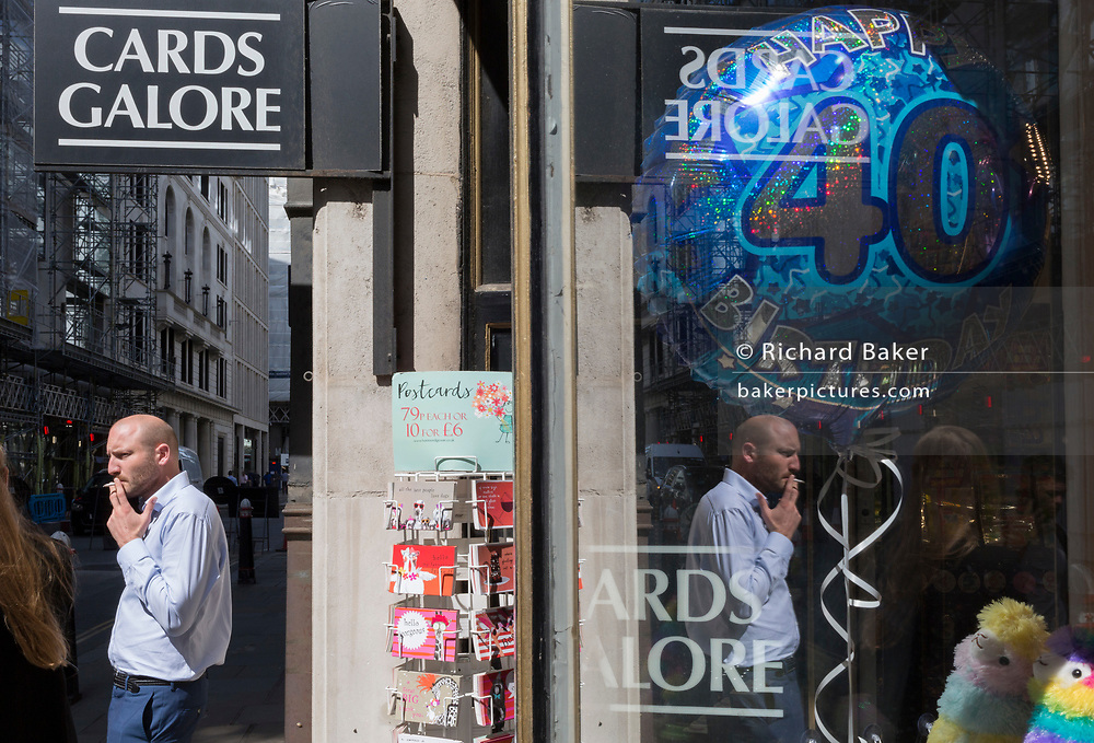 A man stands in sunshine smoking a cigarette in front of a shop selling party balloons including a large 40th birthday version, near Liverpool Street Station in the City of London, the capital's financial district - aka the Square Mile, on 8th August, in London, England.