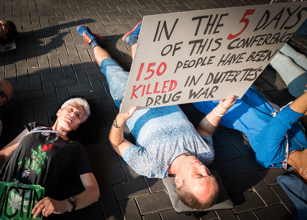 26 July 2018, Amsterdam, the Netherlands: At a die-in demonstration by the entrance of the 2018 International AIDS Conference, a man holds a sign criticizing the war on drug users being conducted by Philippines President Rodrigo Duterte.