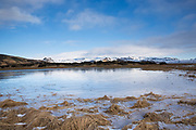 Typical Icelandic landscape of snow covered mountains and melting snow as winter turns to spring in South Iceland