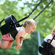 A fourteen month old baby girl enjoys playing on the swing in a playground setting during play. Photo Tim Clayton