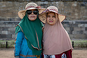 Two Javanese women at Borobudur Temple on the 24th October 2019 in Java in Indonesia. Borobudur is a 9th-century Mahayana Buddhist temple in Magelang Regency. It's the worlds largest Buddhist temple, consisting of nine stacked platforms, six square and three circular, topped by a central dome.
