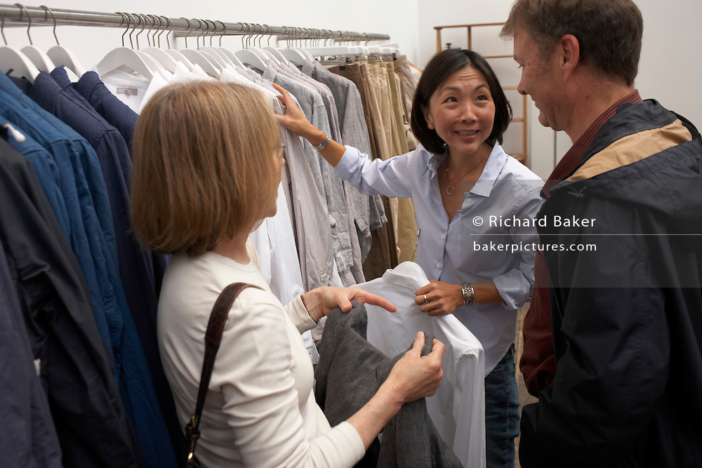 A customer tries on shirts with friends at British couturier Margaret Howell's flagship Wigmore Street London shop
