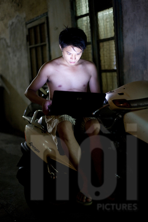 At night, a young bare chested vietnamese man sits outside on a motorbike and looks at his laptop's screen. Vietnam, Asia.