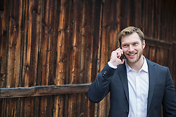 Mid adult businessman talking on mobile phone outside and smiling, Bavaria, Germany