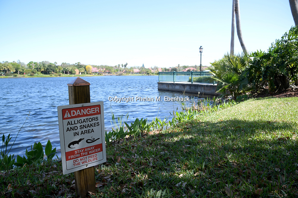 A sign warning of the dangers of alligators and snakes stands along the edge of a lake at Disney's Coronado Springs Resort, Friday, March 3, 2017, in Lake Buena Vista, Fla. (Photo by Phelan M. Ebenhack)