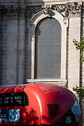 A red London bus passes the Wren-designed curved window architecture in the north trancept of St Paul's Cathedral, on 20th October 2021, in London, England.