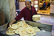 A waiter collects breads from the kitchen to serve at Karims Restaurant, Old Delhi
