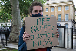 London, UK. 15th July, 2021. A campaigner holds a sign reading Fire Safety Justice Now at a protest opposite Downing Street by leaseholders and tenants living in unsafe homes. Some leaseholders are faced with crippling costs to fix safety issues and they called on the government to ensure that their homes are made safe from fire as a matter of priority, to make interim payments and cover fire safety remediation costs and to find a solution with mortgage lenders.