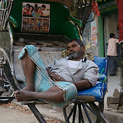"""A rickshaw puller taking rest on his vehicle...The hand-pulled rickshaw of Calcutta, immortalised by Dominic Lapierre's famous novel, City of Joy, will soon be a part of the history books as a bill passed by the West Bengal state assembly described the centuries-old mode of transport as """"inhumane."""".The future of about 18,000 rickshaw pullers in the city, earning an avarage daily wages of about 100 rupees ($2.5).is unclear as they call for a compensation package to help them rehabilitate into alternative jobs."""