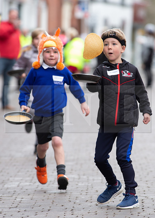 © Licensed to London News Pictures. 05/03/2019. Lichfield, Staffordshire, UK. The annual Shrove Tuesday pancake race taking place in Bore Street in the City Centre of Lichfield. Pictured, Charlie Knight, right tosses his pancake pursued by Alfie Coleman. The event features races for men, women, children and those in fancy dress. The runners are supported by the voice of Town Crier Ken Knowles and the overall winner walks away with a brass and wooden Shrove Tuesday trophy. Photo credit: Dave Warren/LNP