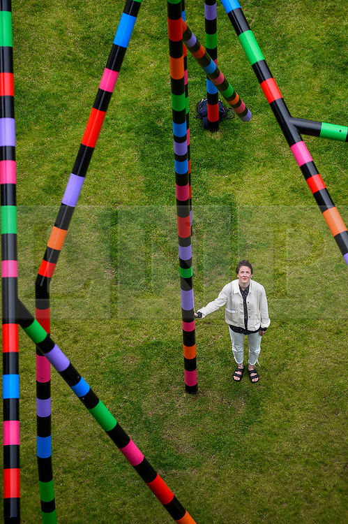 "© Licensed to London News Pictures. 16/07/2020. LONDON, UK.  A staff member poses at the unveiling of ""My World and Your World"", by major contemporary London-based, Irish artist Eva Rothschild.  The new 16m high public sculpture in Lewis Cubitt Park in King's Cross resembles a lightning bolt, painted in black, purple, pink, orange, green and red stripes.  The coronavirus lockdown caused the April 2020 launch to be postponed, but the unveiling has been able to go ahead now that certain lockdown restrictions have been eased by the UK government.  Photo credit: Stephen Chung/LNP"