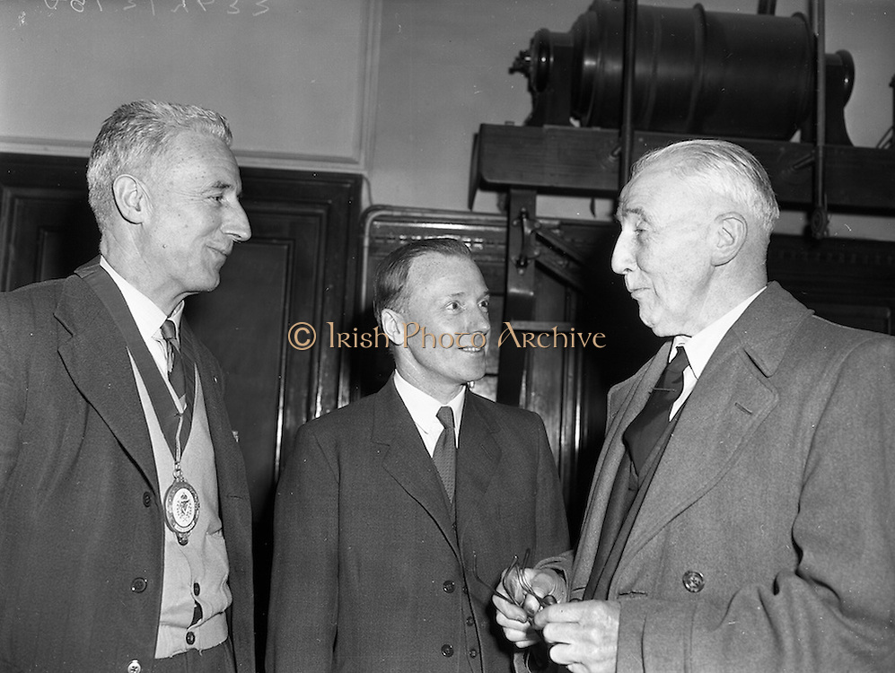 """09/03/1959<br /> 03/09/1959<br /> 09 March 1959<br /> Lecture by Mr. S.E. Holmes on """"Modern Lubricants and Additives"""" at Trinity College, Dublin. Mr. S.E. Holmes, A.R.I.C., A.F.I.N.S.P. of C.C. Wakefield, London, Delivered a lecture entitled """"Modern Lubricants and Additives"""" to members of the Engineering and Scientific Association of Ireland at the Physics Laboratory, Trinity College. Picture shows Mr. Holmes (centre) chatting to Mr. J.C. Tonge, (left), President of the Engineering and Scientific Association of Ireland and Lt-Col. S.W. Carty, Honorary Treasurer and Secretary of the Association before the meeting."""
