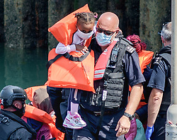 © Licensed to London News Pictures. 20/07/2021. Dover, UK. A migrant toddler is carried by a Border Force officer as she is brought ashore at Dover Harbour in Kent after crossing the English Channel. It is being reported that at least 430 migrants crossed the English Channel to the UK on Monday, a new single day record. Photo credit: Stuart Brock/LNP