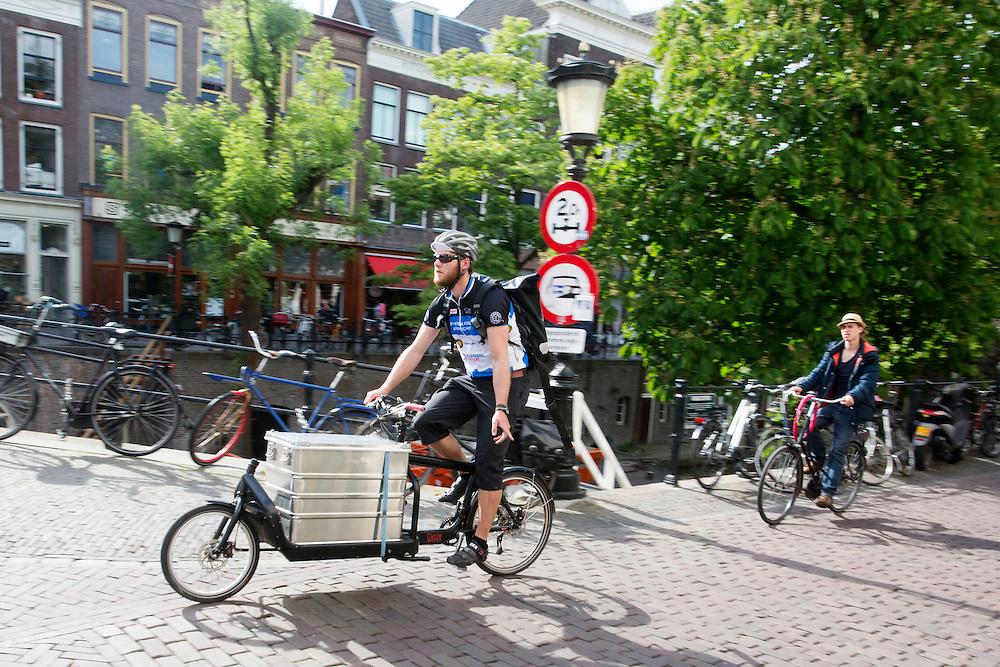 In Utrecht geeft een fietskoerier richting aan als hij met een bakfiets over de Oudegracht fietst.<br /> <br /> In Utrecht a bike courier is cycling on a cargo bike.