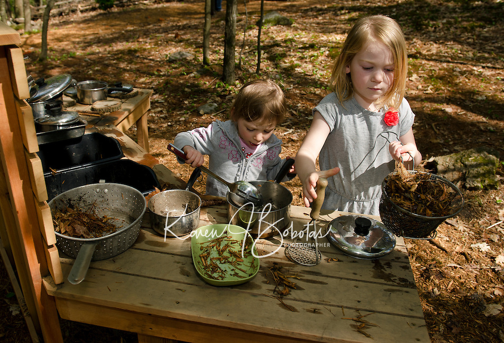 """Devin Turcotte and Willow Clark-Patten in the """"kitchen area"""" making some lunch at Prescott Farm's Natural Playscape following their grand opening on Saturday morning.  (Karen Bobotas/for the Laconia Daily Sun)"""