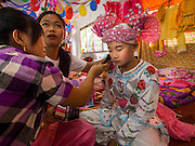 "04 APRIL 2015 - CHIANG MAI, CHIANG MAI, THAILAND:  Family members help a boy get into his ceremonial outfit for the Poi Sang Long Festival at Wat Pa Pao in Chiang Mai. The Poi Sang Long Festival (also called Poy Sang Long) is an ordination ceremony for Tai (also and commonly called Shan, though they prefer Tai) boys in the Shan State of Myanmar (Burma) and in Shan communities in western Thailand. Most Tai boys go into the monastery as novice monks at some point between the ages of seven and fourteen. This year seven boys were ordained at the Poi Sang Long ceremony at Wat Pa Pao in Chiang Mai. Poy Song Long is Tai (Shan) for ""Festival of the Jewel (or Crystal) Sons.     PHOTO BY JACK KURTZ"