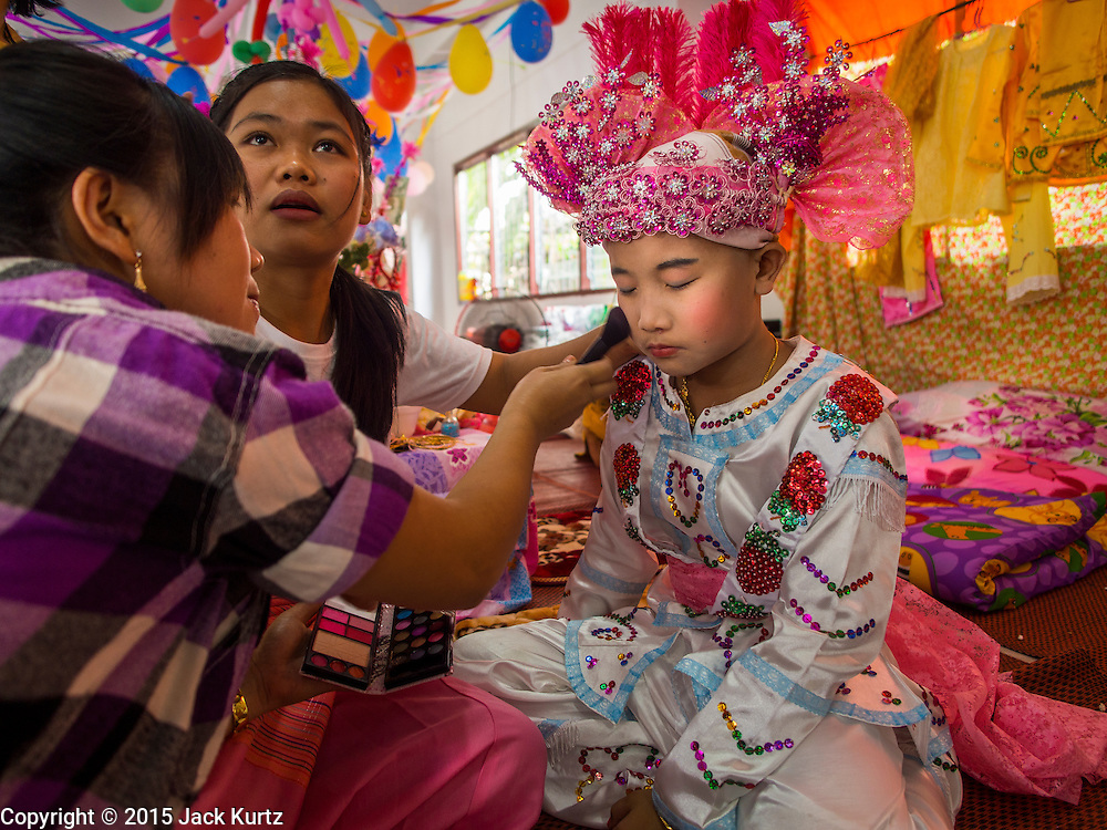 """04 APRIL 2015 - CHIANG MAI, CHIANG MAI, THAILAND:  Family members help a boy get into his ceremonial outfit for the Poi Sang Long Festival at Wat Pa Pao in Chiang Mai. The Poi Sang Long Festival (also called Poy Sang Long) is an ordination ceremony for Tai (also and commonly called Shan, though they prefer Tai) boys in the Shan State of Myanmar (Burma) and in Shan communities in western Thailand. Most Tai boys go into the monastery as novice monks at some point between the ages of seven and fourteen. This year seven boys were ordained at the Poi Sang Long ceremony at Wat Pa Pao in Chiang Mai. Poy Song Long is Tai (Shan) for """"Festival of the Jewel (or Crystal) Sons.     PHOTO BY JACK KURTZ"""