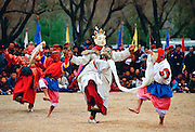 Dancers in masks enacting tales of Buddhist legend at festival, Paro, Bhutan
