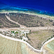 Aerial shot fof Lady Elliot Island. The airstrip crosses the center of the island, with the resort on the bottom left corner. The lighter section at bottom is the lagoon. The blue section at the top is the deeper water.