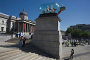Spectators stand at the foot of Artist Yinka Shonibare's artwork called Nelson's Ship in a Bottle on the Fourth Plinth in London's in Trafalgar Square. The artwork features a 1:29 scale replica of Lord Nelson's original HMS Victory commemorating the Battle of Trafalgar in 1805, Shonibare said his version with its textile sails with African and batik prints reflects the multicultural and diverse capital. The 2.35m high ship inside a specially-made glass bottle, will be in place for 18 months. 37 large sails are made of patterns which are commonly associated with African dress and culture. The patterns also look back at the path of colonialism as the patterns were inspired by Indonesian batik design, which were mass produced by the Dutch and sold to the colonies in West Africa. The Fourth Plinth is in the north-west of Trafalgar Square, London.