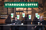 Customers drink coffee in the window of a Starbucks coffee shop in the city of London.