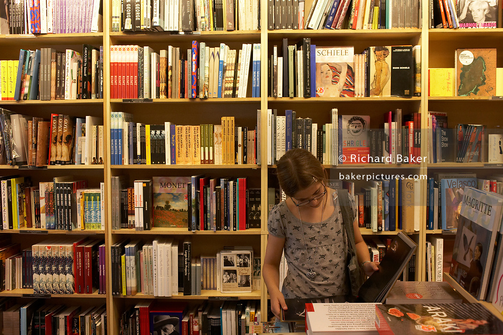 Surrounded by books, a young 12 year-old girl browses intensely Art books in Borders bookshop in Central London, England.