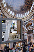Seen through an aperture of a construction hoarding, workmen continue work within the grounds of St Paul's Cathedral where the new north entrance will be completed soon, on 26th October 2020, in London, England.