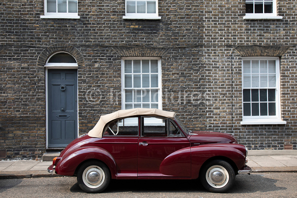 Two vintage Morris Minor 1000s parked together in a Georgian terraced street in London, United Kingdom. The Morris Minor is a British car of which more than 1.6million were manufactured between 1948 and 1972. Initially available as a two-door saloon and tourer, or convertible, the range was expanded to include a four-door saloon. It was the first British car to sell over one million units and is considered a classic example of automotive design, as well as typifying Englishness.