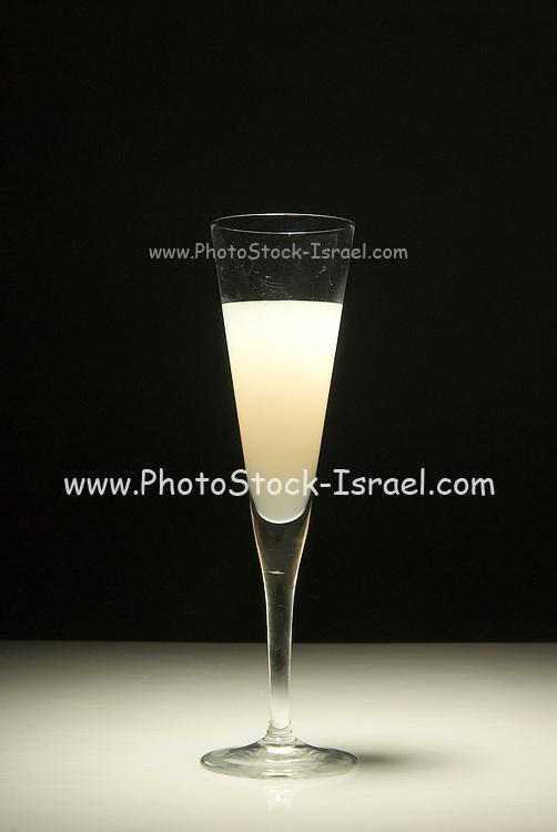 An elegant glass of grapefruit juice on a black background
