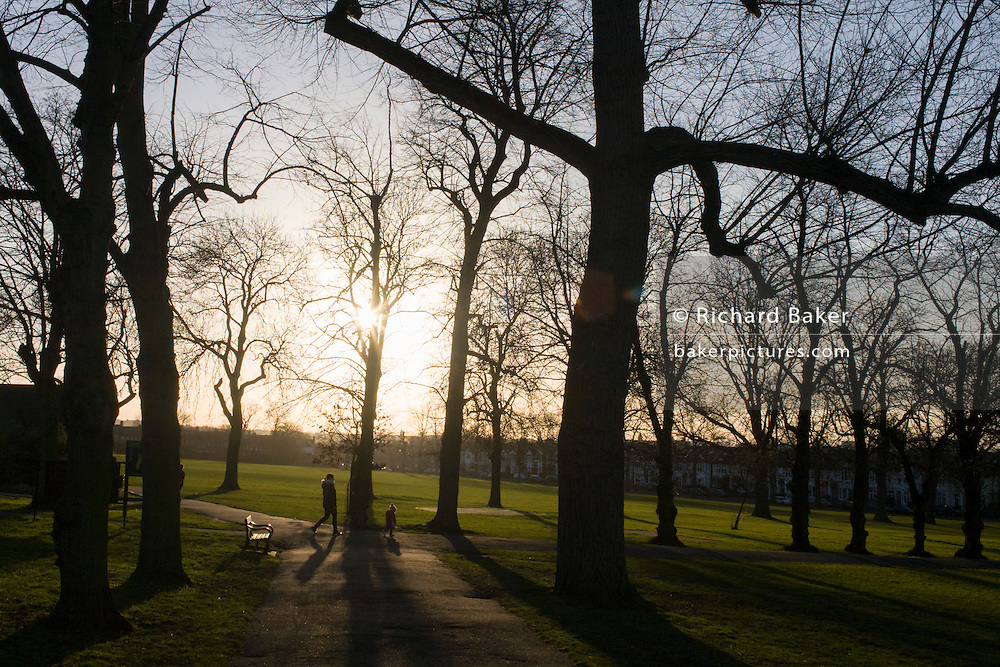Mother and child enjoy spring weather in Ruskin Park in the south London borough of Lambeth.