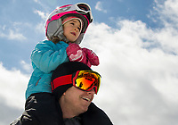 Evlin Landry sits on her dad Sean's shoulders as they watch skiers and riders try to cross the pond during Gunstock Mountain's BYODC event during their final weekend of the 2019 season.  (Karen Bobotas/for the Laconia Daily Sun)
