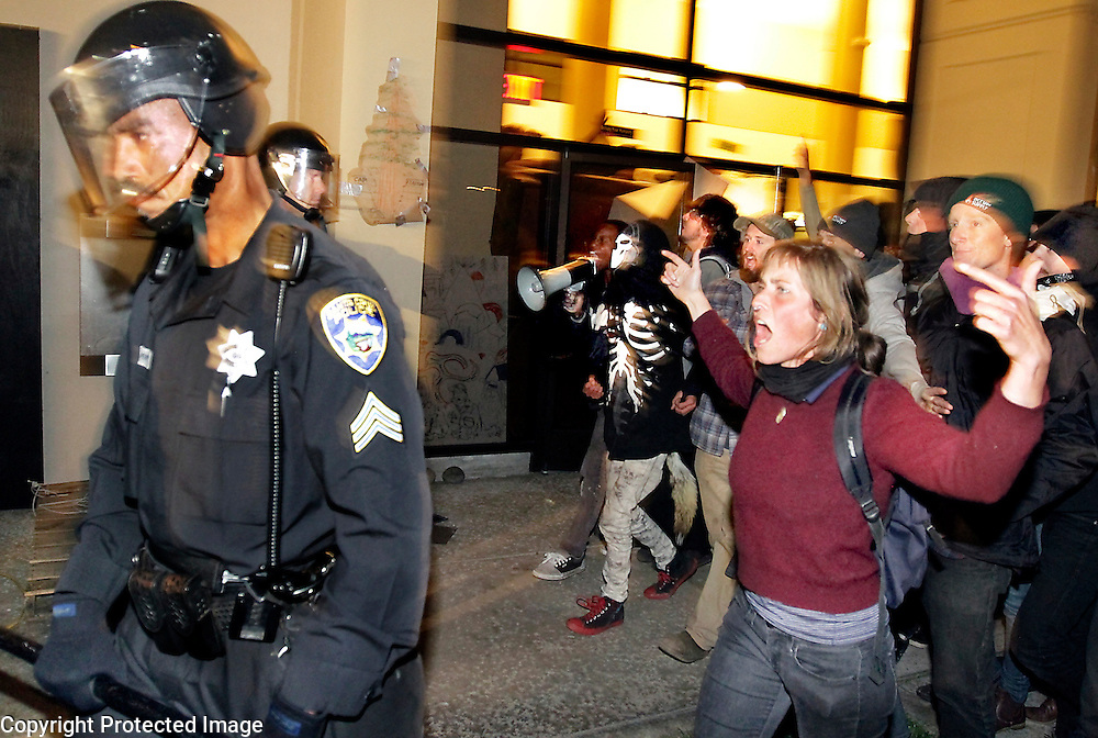 Protesters yell at Sgt. Dave Perry and other Santa Cruz Police officers on November 30, 2011 as they leave a former bank building occupied that day by 20-30 protesters. After a brief confrontation, the police left to regroup. The standoff ended three days later when the occupyers left on their own as police were massing to evict them forcibly.<br /> Photo by Shmuel Thaler <br /> shmuel_thaler@yahoo.com www.shmuelthaler.com
