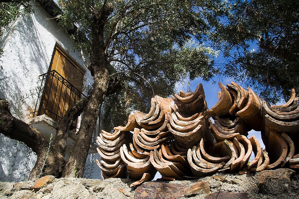 Clay roof tiles lay in a pile on a wall in the village of Portugos, Las Alpujarras, Andalusia, Spain.