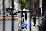 An armed policeman stands guard in Downing St, London. The area is heavily protected by layers of security.