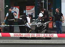 © Licensed to London News Pictures. 21/07/2021. London, UK. Police officers examine a quad bike in the road at a fatal stabbing in Brixton, south London. An investigation is underway after a man died following a stabbing in Brixton. Police were called at 20:18hrs on Wednesday, 21 July to reports of an assault close to Brixton Underground Station. Officers attended and found a man, believed to be aged in his early 20s, suffering from a stab injury. They immediately provided first aid. The London Ambulance Service and London's Air Ambulance also attended but despite their efforts the man was pronounced dead at the scene at the 20:45hrs. His next of kin has been informed and are being supported by officers. Formal identification has not taken place. A man was arrested nearby on suspicion of causing grievous bodily harm. Photo credit: Andy Gatt/LNP
