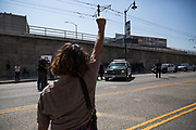 Demonstrators raise up her fist to police in front of Metropolitan Dentention Center during an immigration rally on Monday, July 2nd, 2018 in Downtown Los Angeles, California.