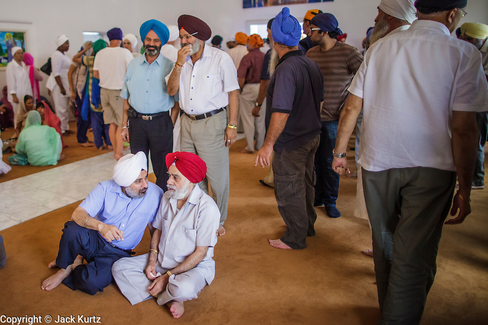 12 AUGUST 2012 - PHOENIX, AZ: Indian men chat after Sunday services at the Guru Nank Dwara Ashram Sikh temple in central Phoenix. Guru Nank Dwara Ashram is the oldest of three Sikh temples in the Phoenix area. There are about 1,500 Sikh families in the area. Memorials have been held throughout the week to honor the Sikhs killed in the mass shooting in Wisconsin last week. Sunday's service included several mentions of the massacre and was attended by a number of people active in the Phoenix interfaith community.    PHOTO BY JACK KURTZ