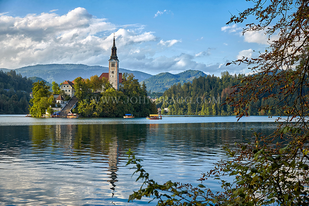 The Lake Bled island is surrounded by pletna boats and is capped by a Church at the top of ninety-nine steps.