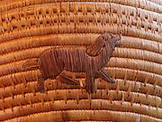Figure of dog on large antique Yupik Eskimo grass basket from Western Alaska.