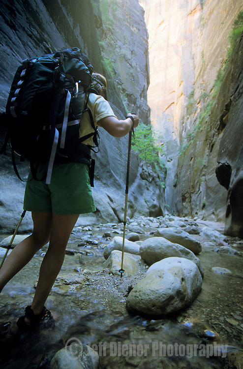 A backpacker hikes through the narrows of Orderville Canyon in Zion National Park, Utah.