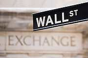 Wall Street sign in front of the engraved word Exchange on the New York Stock Exchange building in New York City, NY, USA.
