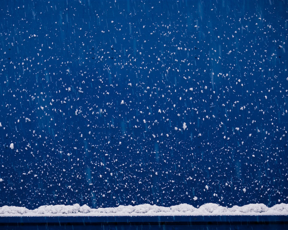 Falling snow agains a blue background