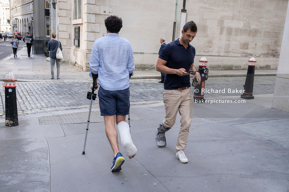 A man wearing a plaster cast and using mobility aids, hobbles past another male wearing a foot boot in the City of London, the capital's financial district, on 21st September 2021, in London, England.