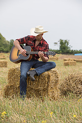 hot cowboy sitting on a hay bale with a guitar