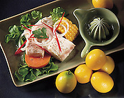 Grilled fish with lemon, corn and salad,