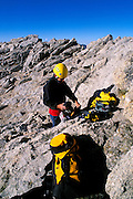 Climber packing gear on the summit of Mt. Conness, Tuolumne Meadows area, Yosemite National Park, California