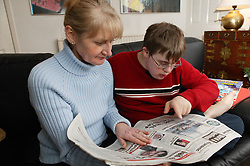 Single parent and son reading newspaper together on a sofa,